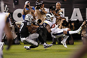 Oakland Raiders tight end Jared Cook (87) pulls on his jersey as he tackles Los Angeles Rams rookie defensive back John Johnson III  (43) after Johnson intercepts a second quarter pass intended for Cook during the 2018 regular season week 1 NFL football game against the Oakland Raiders on Monday, Sept. 10, 2018 in Oakland, Calif. The Rams won the game 33-13. (©Paul Anthony Spinelli)
