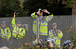 © Licensed to London News Pictures. 04/09/2014. Bristol, UK.  Police watch protesters by the steel fence and barrier by Celtic Manor, at the protest march through Newport against the NATO summit being held at The Celtic Manor resort at Newport. Photo credit : Simon Chapman/LNP