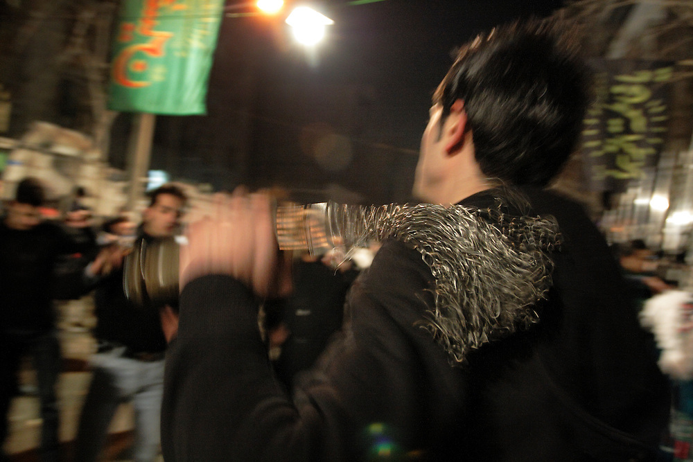 Night celebrations in the street.A man hits himself whit the chains in sign of mourning.