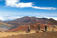 Native Hawaiian Outreach Coordinator Kuhea Paracuelles (left), Honeygirl Duman (middle), and Haleakala Park Superintendent Sarah Creachbaum (right), head down the sliding sands trailhead to check on plant life and guests.  The entirity of the erosional depression is visible, along with the colorful Pu'u, (cinder cones).