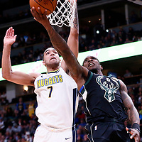 01 April 2018: Milwaukee Bucks guard Eric Bledsoe (6) goes for the reverse layup past Denver Nuggets forward Trey Lyles (7) during the Denver Nuggets 128-125 victory over the Milwaukee Bucks, at the Pepsi Center, Denver, Colorado, USA.