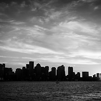 Boston skyline black and white photo with downtown Boston city skyscraper buildings across Boston Harbor.