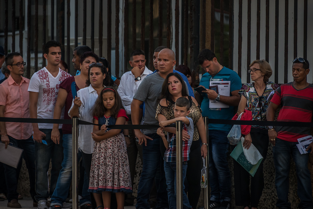 HAVANA, CUBA - JULY 20, 2015: These were the very first people in line out of hundreds of Cuban nationals waiting in line outside of the U.S. embassy to apply for visas on Monday morning. After more than half a century defined by mistrust and rancor, the United States officially reopened its six-story embassy in Havana today, marking a watershed moment of transition for the two countries as they lean toward closer diplomatic ties and ease past one of the last remnants of the Cold War.  President Barack Obama, when announcing an end to the diplomatic freeze, eased travel restrictions, opened the door for more remittances to Cuba and expanded the amount of goods that visiting Americans could bring back home – like Cuban cigars and rum. He even removed the country from the list of nations that sponsor terrorism. President Raul Castro, meanwhile, has spent the last five years, before the thaw even began with the Obama administration, attempting to alter his nation's economic dysfunction, ordering the firing of government employees, encouraging a slow but fresh influx of Cubans into self-employment and even creating a special economic zone in the coastal city of Mariel to attract foreign investment.  PHOTO: Meridith Kohut for The New York Times