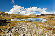 Reflection of clouds on one of three April Bowl tarns at Summit Lake Recreation Site in Hatcher Pass in Southcentral Alaska. Summer. Afternoon.