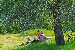 ©Licensed to London News Pictures 06/05/2020  <br /> Greenwich, UK. This lady reading a book under a tree. People out and about in Greenwich park, Greenwich, London exercising and enjoying the warm sunny weather.  Photo credit:Grant Falvey/LNP