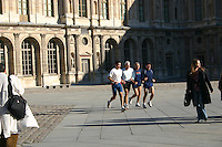 Four men jogging at the Louvre museum, Paris, France.<br />