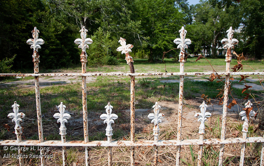 fleur de lis design in decaying, painted metal fence in Mandeville, Louisiana