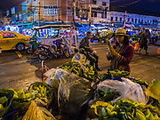 29 FEBRUARY 2016 - BANGKOK, THAILAND:  A woman sells lotus buds from her sidewalk stall in front of the Bangkok flower market. She closed the stand a few minutes after the photo was made. Many of the sidewalk vendors around Pak Khlong Talat, the Bangkok flower market, closed their stalls Monday. As a part of the military government sponsored initiative to clean up Bangkok, city officials announced new rules for the sidewalk vendors that shortened their hours and changed the regulations they worked under. Some vendors said the new rules were confusing and too limiting and most vendors chose to close Monday rather than risk fines and penalties. Many hope to reopen when the situation is clarified.   PHOTO BY JACK KURTZ