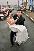 Una pareja de recien casados posa contenta en una peligrosa calle de la ciudad de Lima.