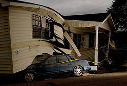 10 December, 05. New Orleans, Louisiana.  Post Katrina aftermath.<br /> 3 1/2 months after the storm. From fancy lights, to meagre lights to no Christmas lights. A car remains pinned underneath a house in the Gentilly neighbourhood. Residents of the neighbourhood complain that they see no attempts to help them, no federal help, local government help, nothing. Curfews remain in place after dark, painfully slowly mountains of trash are cleared from the streets, there is no electricity or gas, although the water is allegedly 'safe' to drink.<br /> Photo; ©Charlie Varley/varleypix.com