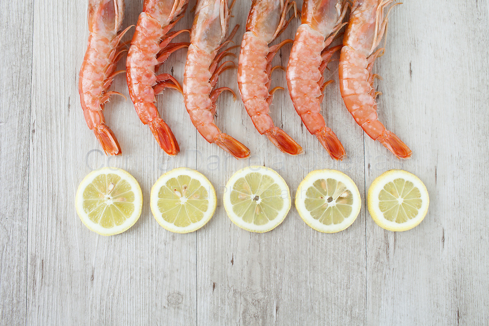 Fresh prawn tails with lemon slices, flat lay.