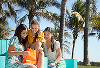 Three teenage girls (16-17) sitting in park looking at shopping bags