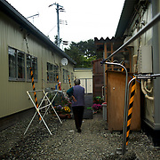 A displaced woman walks by prefabricated houses in Togura, used as temporary shelter for families who lost their homes during the devastating earthquake and tsunami that hit the east coast of Japan in 2011. On the third anniversary of the disaster, nearly 270,000 remain displaced.