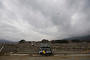 A rescue helicopter flies over a battered car that lies balanced on the rim of raised stretch of highway overlooking the wilderness created by March 11's quake and tsunamis in Rikuzen-Takata City, Iwate Prefecture on  21 March 20011.  .Photographer: Robert Gilhooly