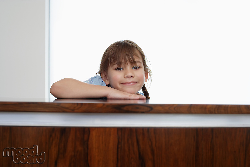 Girl (5-6) resting head on wooden surface