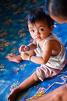 Cute little baby girl sitting on the floor in Nanga Sumpa Longhouse.