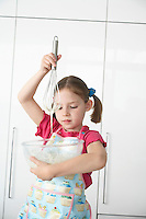 Girl (5-6) preparing food in bowl using wire whisk