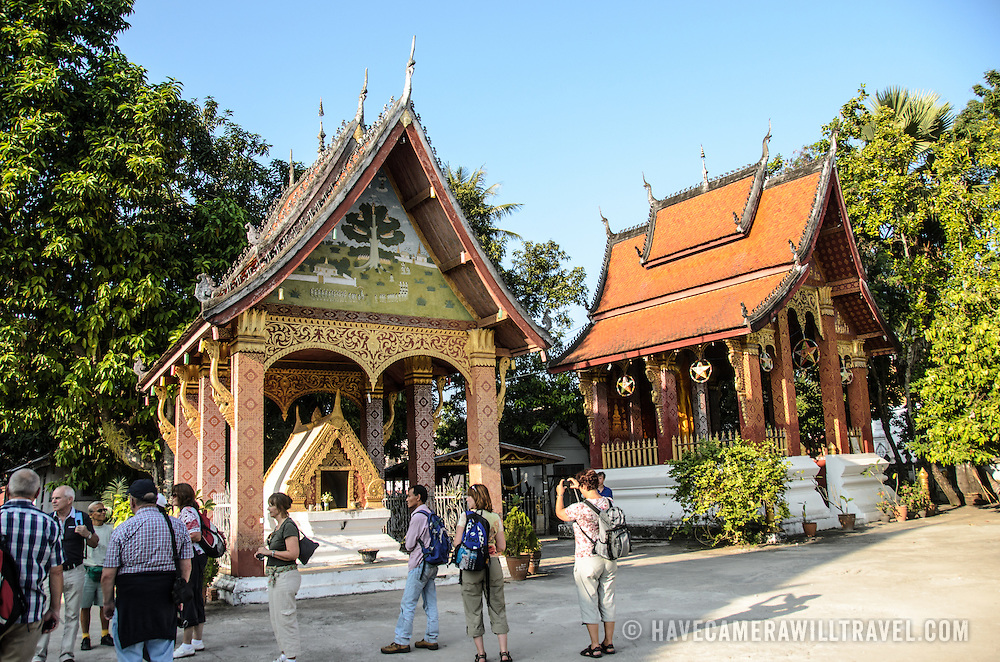 A group of tourists at Luang Prabang's Wat Sensoukharam, with two pagoda structures.