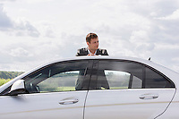 Young businessman leaning on broken down car at countryside