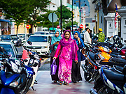 """22 AUGUST 2018 - GEORGE TOWN, PENANG, MALAYSIA:  Malaysian Muslims walk to Kapitan Keling Mosque in George Town for Eid al-Adha services. It is the oldest mosque in George Town. Eid al-Adha, """"Feast of the Sacrifice"""" is the second of two Islamic holidays celebrated worldwide each year. It honors the willingness of Ibrahim (Abraham) to sacrifice his son as an act of obedience to God's command.     PHOTO BY JACK KURTZ"""