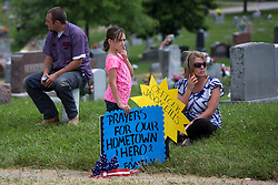 Brooklyn Blair, 9, of Chaplin holds a sign in support of fallen Bardstown police officer Jason Ellis who was laid to rest, Thursday, May 30, 2013 at High View Cemetery in Chaplin. Photo by Jonathan Palmer