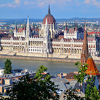 Elevated View of Hungarian Parliament Building in Budapest, Hungary <br /> The architectural gem anchoring the East Bank of the Danube is the Hungarian Parliament Building in Pest. Architect Imre Steindl created this stunning Gothic Revival design. The house for the National Assembly of Hungary opened in 1896. This panoramic view is from the terrace of Fisherman's Bastion on the Buda side. In the foreground is the Reformed Church. The tower of the Buda Calvinist Church stands 203 feet in sharp contrast to its pyramid-shaped roof covered with colorful Zsolnay tiles.