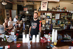 "03 Sept  2005. New Orleans, Louisiana. Post hurricane Katrina.<br /> Johnny White's Sports Bar on Bourbon Street in the French Quarter - with it's claim to ""Never Close."" The bar has remained open throughout.  Barman Jo Bellomy at the helm.<br /> Photo Credit ©: Charlie Varley/varleypix.com"