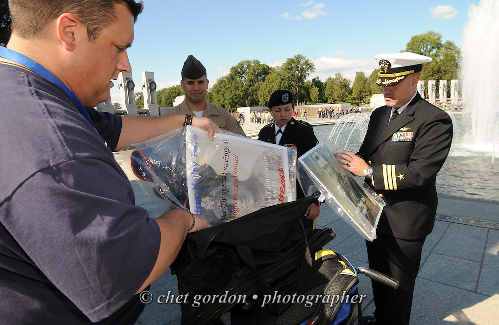 Hudson Valley Honor Flight Chairman Frank Kimler and active duty military members secure the portraits of WWII Army Veterans Tech. Sgt. Stephen M. Moravick and 1st. Lt. William Seefeld at the WWII Memorial in Washington, DC on Saturday, October 18, 2014. Seventy-five WWII Veterans from the Westchester County area toured the WWII Memorial and Arlington National Cemetery onboard the inaugural flight from Westchester County Airport in White Plains, NY. Hudson Valley Honor Flight is a chapter of the Honor Flight Network, which provides free flights for WWII Veterans and tours of the WWII Memorial constructed in their honor, and other sites in the nation's capital.  © www.chetgordon.com