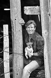 All American man holding a Jack Russell Puppy in a barn