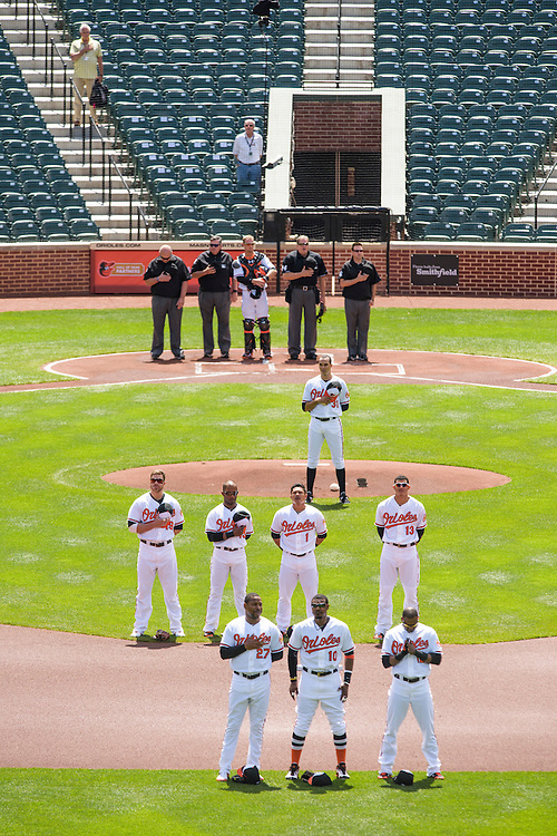 Baltimore, MD - April 29, 2015: The Baltimore Orioles and Chicago White Sox stand during a recorded version of the National Anthem at an empty Oriole Park at Camden Yards on April 29, 2015. The civil unrest in Baltimore has forced the game between the Chicago White Sox and Baltimore Orioles to be closed to the public and moved to the afternoon. (Matt Roth for ESPN)