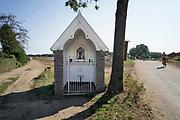 Nederland, Lomm, 1-9-2018 In een wegkapelletje langs de weg staat dit Mariabeeldje. Er kunnen kaarsjes gebrand worden. Een fietser, wielrenner, komt voorbij .FOTO: FLIP FRANSSEN