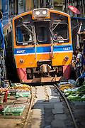 17 JANUARY 2013 - SAMUT SONGKHRAM, SAMUT SONGKHRAM, THAILAND: A train pass pulls into the market in Samut Songkhram. Four trains each day make the round trip from Baan Laem, near Samut Sakhon, to Samut Songkhram, the train chugs through market eight times a day (coming and going). Each time market vendors pick up their merchandise and clear the track for the train, only to set up again when the train passes. The market on the train tracks has become a tourist attraction in this part of Thailand and many tourists stop to see the train on their way to or from the floating market in Damnoen Saduak.    PHOTO BY JACK KURTZ