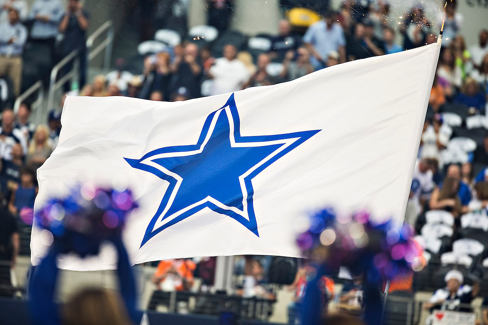 ARLINGTON, TX - OCTOBER 6:  Flag of the Dallas Cowboys is run around the field before a game against the Denver Broncos at AT&T Stadium on October 6, 2013 in Arlington, Texas.  The Broncos defeated the Cowboys 51-48.  (Photo by Wesley Hitt/Getty Images) *** Local Caption ***