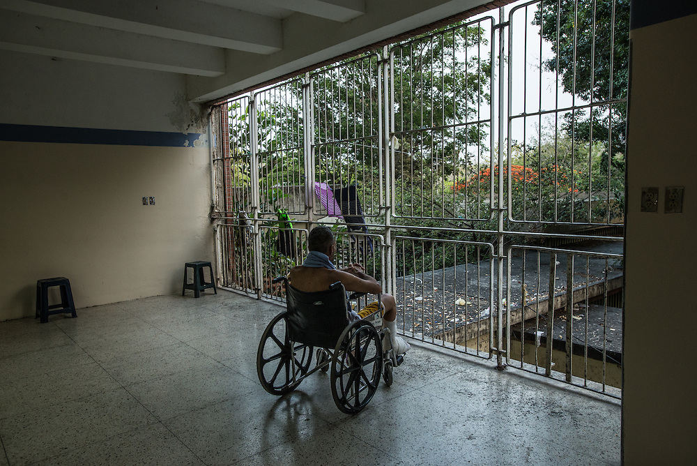 PUERTO LA CRUZ, VENEZUELA - APRIL 15, 2016: A patient in a wheelchair looks out of Hospital Universitario Dr. Luís Razetti - one of the worst state-run, public hospitals in Venezuela.  Doctors compare it to working in a war zone - they regularly have to turn patients away, because they don't have the majority of medicines  or medical equipment and supplies needed to give them medical attention.  When they do accept patients, they have to work with extremely limited resources, because they don't have the supplies they need for things like X-Rays,  and many exams nd operations.  The hospital's infrastructure is crumbling, and staff don't have all the cleaning supplies required to keep the hospital sanitary. The hospital also suffers from weekly shortages of running water and electricity.  In April, several babies died when a power outage turned off the incubators, and the hospital's generator failed to work because of lack of maintenance.  The same month, authorities found over 100 pieces of medical equipment, stolen from the hospital in the home of the assistant to the hospital's director.  Despite having the largest oil reserves in the world, falling oil prices and wide-spread government corruption have pushed Venezuela into an economic crisis, with the highest inflation in the world and chronic shortages of food and medical supplies.  PHOTO: Meridith Kohut for The New York Times