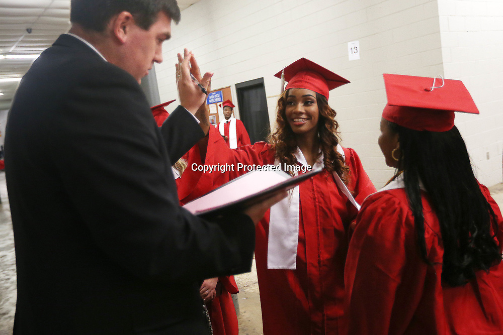 Shannon High School senior Kinins Steward high-fives Shannon Middle School principal Jason Arledge before the start of Shannon's graduation ceremony Saturday evening at the BancorpSouth Arena.