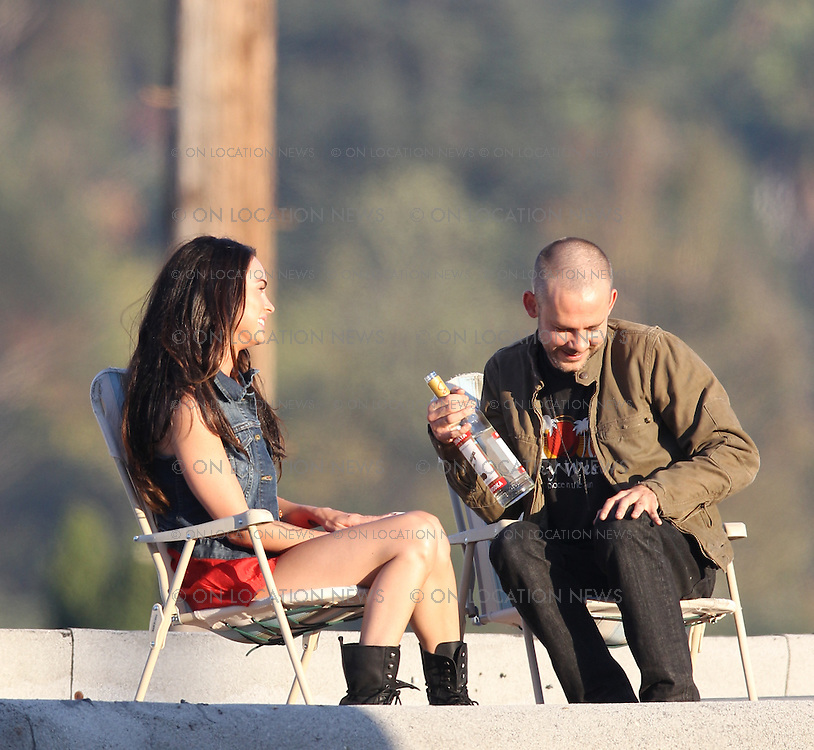 "July 23rd 2010  Los Angeles, CA.  ***EXCLUSIVE*** Megan Fox and Dominic Monaghan share some Vodka and a passionate kiss while sitting on lawn chairs on the rooftop of a Liquor store in a gritty  Los Angeles neighborhood. Fox and Monaghan spent the day filming scenes together for their starring roles in Eminem and Rihanna's music video for ""The Way You Lie"".  Megan and Dominic also filmed a scene inside the liquor store as well as inside  a run down dive bar next door. Photo by Eric Ford/ On Location News 818-613-3955"