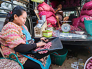 "21 DECEMBER 2015 - BANGKOK, THAILAND:   A woman sorts scallions in her stall in Pak Khlong Talat, also called the Flower Market. The market has been a Bangkok landmark for more than 50 years and is the largest wholesale flower market in Bangkok. A recent renovation resulted in many stalls being closed to make room for chain restaurants to attract tourists. Now Bangkok city officials are threatening to evict sidewalk vendors who line the outside of the market. Evicting the sidewalk vendors is a part of a citywide effort to ""clean up"" Bangkok.     PHOTO BY JACK KURTZ"