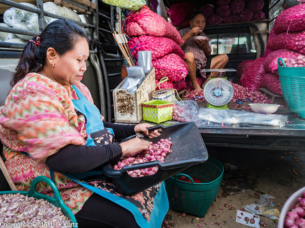 """21 DECEMBER 2015 - BANGKOK, THAILAND:   A woman sorts scallions in her stall in Pak Khlong Talat, also called the Flower Market. The market has been a Bangkok landmark for more than 50 years and is the largest wholesale flower market in Bangkok. A recent renovation resulted in many stalls being closed to make room for chain restaurants to attract tourists. Now Bangkok city officials are threatening to evict sidewalk vendors who line the outside of the market. Evicting the sidewalk vendors is a part of a citywide effort to """"clean up"""" Bangkok.     PHOTO BY JACK KURTZ"""
