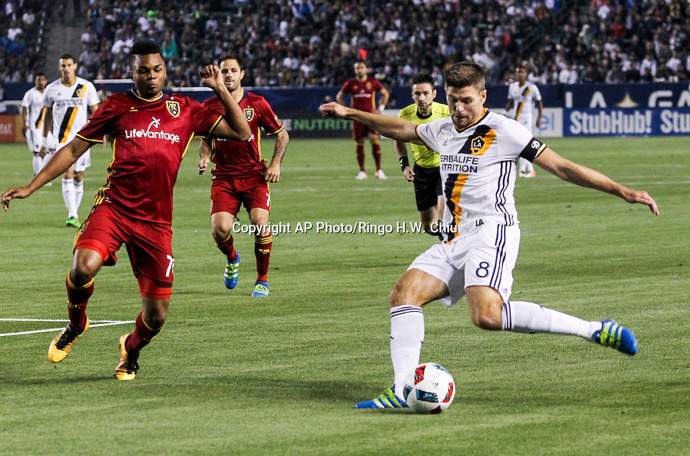 Los Angeles Galaxy midfielder Steven Gerrard, right, kicks the ball against Real Salt Lake forward Juan Manuel Martinez in the first half of an MLS soccer game in Carson, Calif., Saturday, April 23, 2016. (AP Photo/Ringo H.W. Chiu)