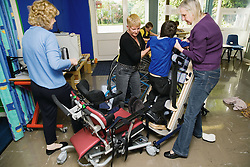 Staff at special school helping child with physical disability out of a wheelchair and into s supported frame,