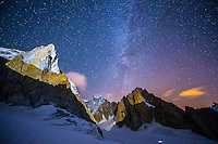 A long exposure night photograph of the NE face La Tour Ronde and neaby summits of Grand Capucin and Mount Maudit taken on a cold and clear Summer night in Mont Blanc Massif, France.