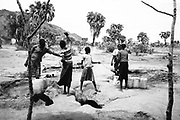 "NUBA MOUNTAINS, SUDAN – JUNE 9, 2018: Nuba women gather water from a shallow well. <br /> <br /> In 2011, the government of Sudan expelled all humanitarian groups from the country's Nuba Mountains. Since then, the Antonov aircraft has terrorized the Nuba people, dropping more than 4,080 bombs on hospitals, schools, marketplaces and churches. Today, vestiges of the Antonov riddle the landscapes of daily life, where more than 1 million Nuba live in famine conditions – quietly enduring the humanitarian blockade intended to drive them out of the region. The skies are mostly clear. Yet the collective memory of the bombings remains an open wound, and the Antonov itself a persistent threat. So frequent were the attacks that the Nuba nicknamed the high flying aircraft and its dismal hum: ""Gafal-nia ja,"" they would declare, running to the hillsides. ""The loss of appetite has come."""