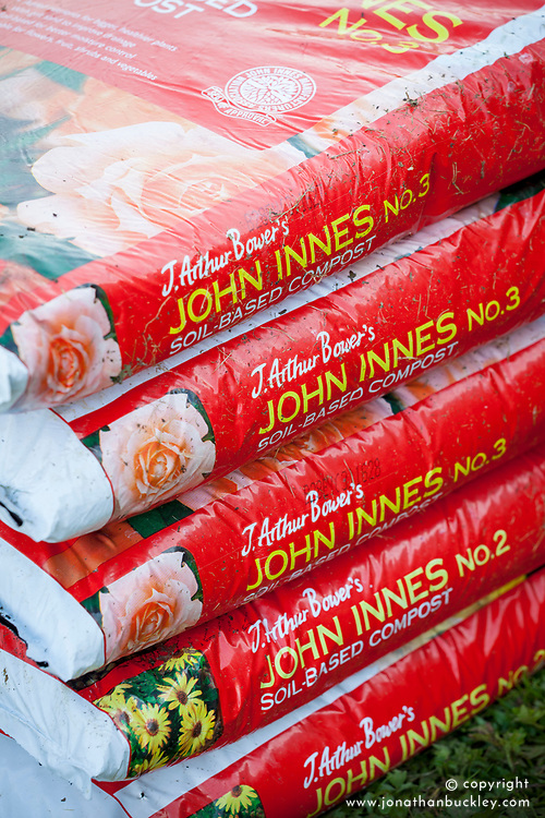 Packs of John Innes No 2 and 3 compost stacked in a pile