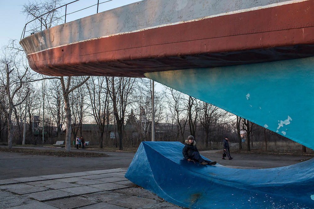 A boy plays under a monument of a boat in a park near the Sea of Azov on Sunday, March 8, 2015 in Mariupol, Ukraine. Photo by Brendan Hoffman, Freelance