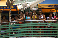 A group of girls observes the crowd passing by on the Miami Beach Urban Weekend 2008.The Miami Beach Urban weekend in the largest Urban Festival in the World, that caters toward the Hip Hop Generation. Over 300.000 participants make the annual trek to South Beach for 4 days full of fun, food, festivities, entertainment, music, and more.