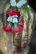 Hand of Buddha Statue with red & white flowers, Thailand