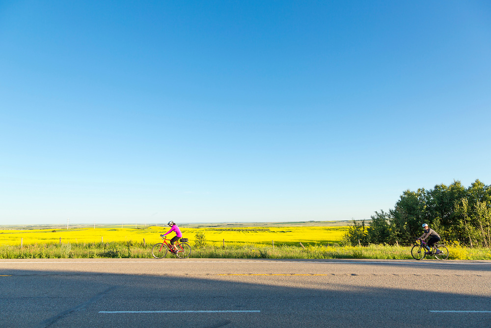 Cyclists gather in the evening light at the Alberta-Saskatchewan border, west of Macklin, prior to morning departure for Wilkie.