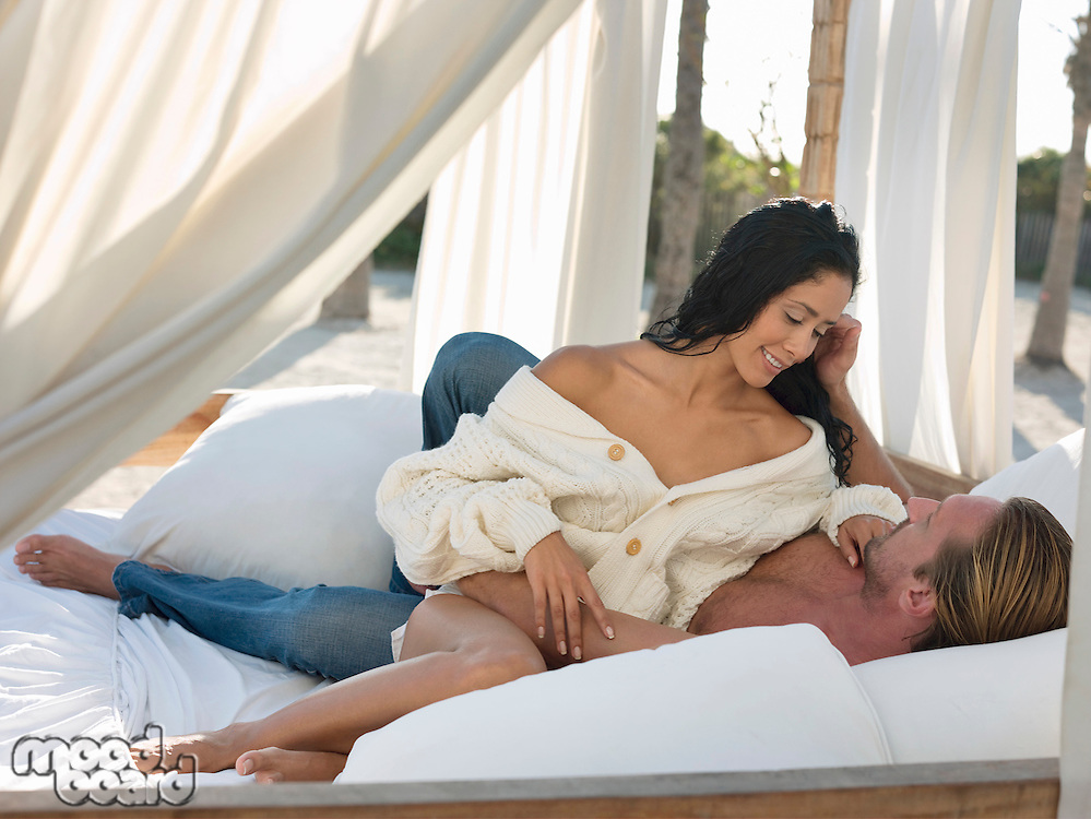 Mid-adult couple on bed at beach