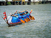 29 OCTOBER 2018 - PHRA PRADAENG, SAMUT PRAKAN, THAILAND: A long boat racing team paddles their boat up river towards the starting line during the long boat races in Phra Pradaeng. The longboat races go about one kilometer down the Chao Phraya River to the main pier in Phra Pradaeng. The boats are crewed by about 20 oarsmen. Longboat racing traditionally marks the end of the Buddhist Rains Retreat (called Buddhist Lent) in Thai riverside communities.       PHOTO BY JACK KURTZ