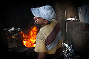 A man smelts soda cans into molten aluminum at a workshop in Izbet az-Zabaleen.